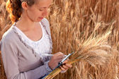 Woman agronomist writes results of his experiment in the wheat field — Stock Photo