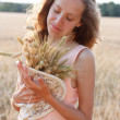 Young girl with ripe wheat ears in the hands in the field — Stockfoto