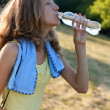 Pretty young woman drinking water after fitness workout — Stock Photo