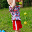 Child playing scattered of fruit with basket on the outdoors — Stock Photo