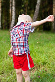 Excited happy child playing outdoor raised his head up — Stock Photo