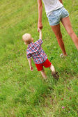 Small child with his mom walking on the green meadow — Stock Photo