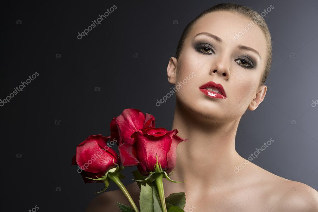 Pretty blonde girl's low key portrait with three red roses, she is in front of the camera with head slightly folded at right and looks in to the lens — Stock Photo #11375381