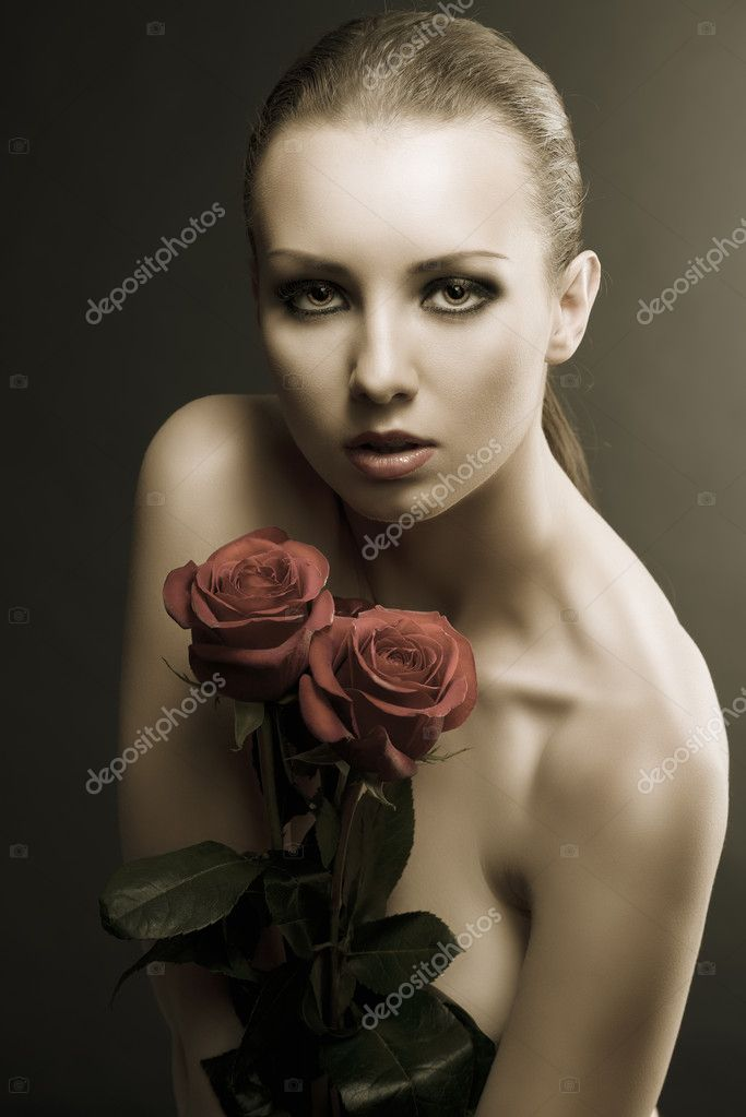 Pretty blonde girl's low key portrait with three red roses, she is in front of the camera, looks in to the lens and takes the roses on her breast — Stock Photo #11463226
