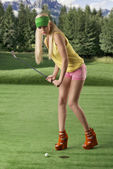 Sexy golf player woman, she is hitting golf ball — Stock Photo