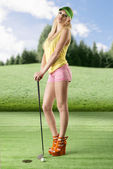 Sexy golf player woman with both hands on the golf club — Stock Photo