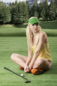 Sexy golf player woman, she is sitting on the grass — Stock Photo