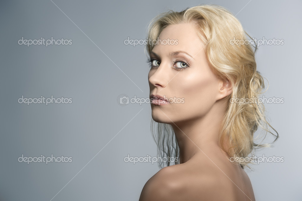 Beautiful blonde girl with nudes shoulders and natural makeup, turned of three quarters at right and looks in to the lens — Stock Photo #11561732