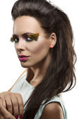 Pretty brunette with feathered makeup looks in to the lens — Stock Photo