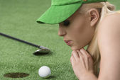 Girl's playing with golf ball, she blows on that — Stock Photo