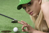 Girl's playing with golf ball looks in to the lens — Stock Photo