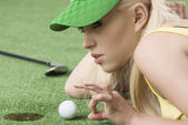Girl's playing with golf ball, she is in profile — Stock Photo
