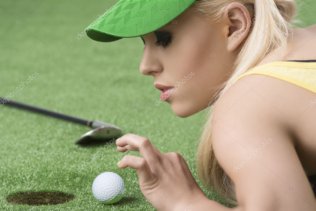 Pretty blonde girl is lying on the grass and playing with golf ball, she is in profile and looks the ball — Stock Photo #11797192