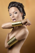 Sexy brunette with two golden bracelets, with open mouth — Stock fotografie