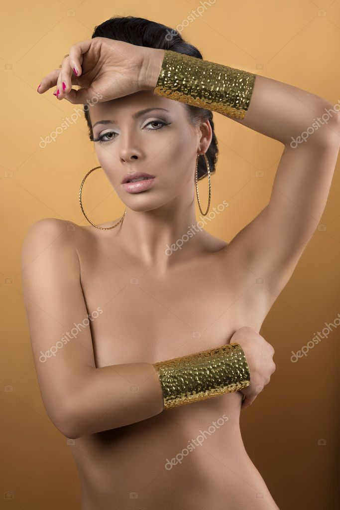Nude sexy girl with two big golden bracelets and hoope earrings, she is in front of the camera, looks in to the lens and has one arm on the chest and the left hand on the front  Stock Photo #11924552