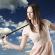 Beautiful woman with golfclub looks down at right — Stock Photo