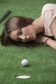 Girl lying on grass with golf ball, she hits — Stock Photo