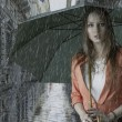 Stock Photo: Beautiful womwith umbrellunder rain