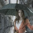 Beautiful woman with umbrella in town under rain — Stock Photo #12290763