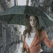 Beautiful woman with umbrella in town under rain — Stock Photo