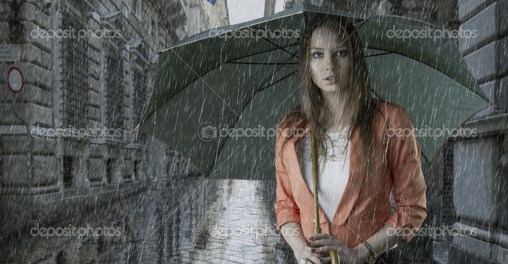 Pretty young woman with green umbrella, under the rain falling down in a old fashion street — Stock Photo #12290632
