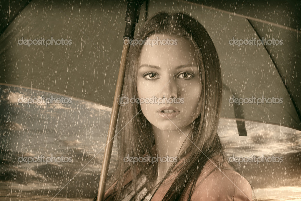 Vintage portrait of pretty young woman with green umbrella,close up under summer rain on sunset  Stock Photo #12291238