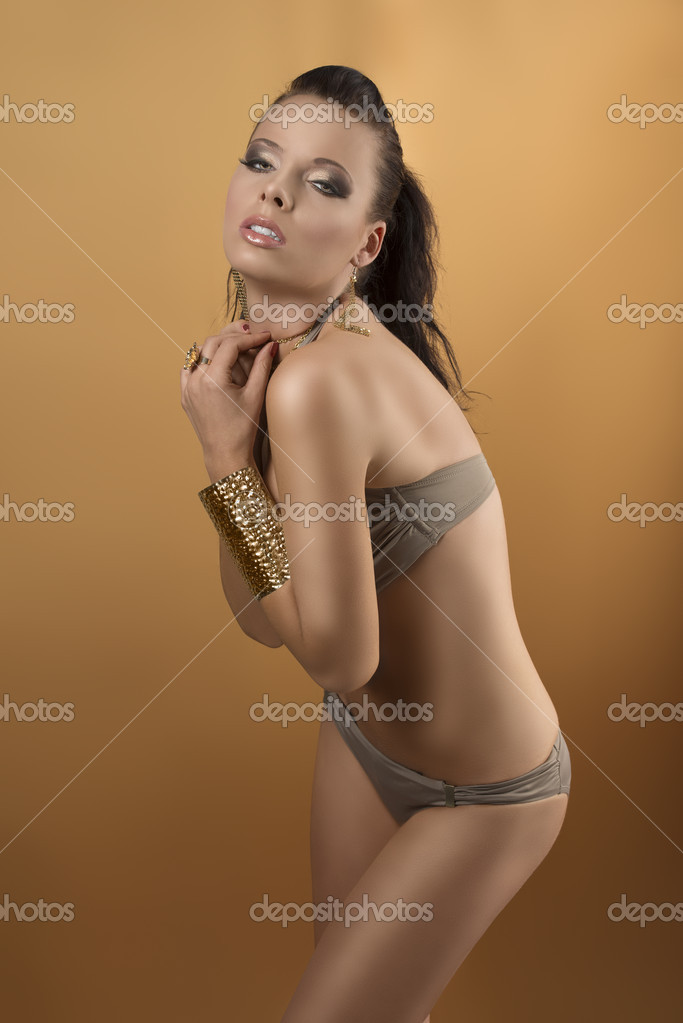 Sexy girl in bikini with brown hair and two gold bracelets, she is turned of three quarters, her arms are combined on the chest and she looks in to the lens — Stock Photo #12322713