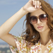 Beautiful girl in sunglasses on background blue sky — Stock Photo #11999769