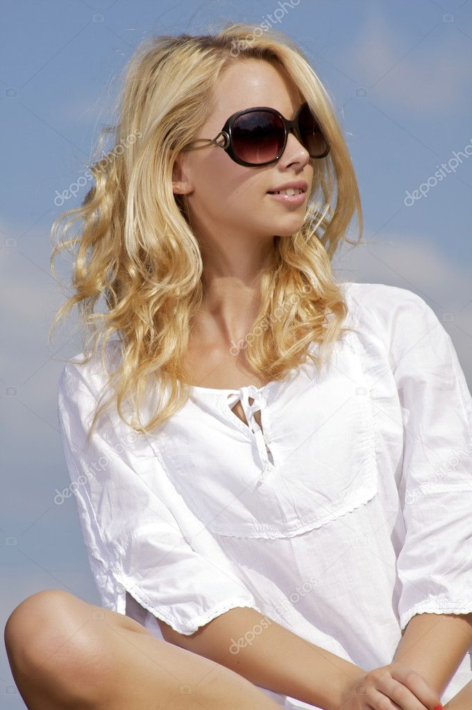 Portrait of beautiful blonde girl in sunglasses on background blue sky  Stock Photo #11999654