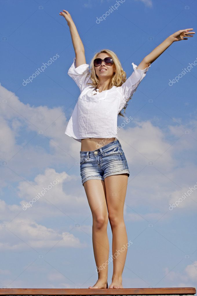 Portrait of beautiful blonde girl in sunglasses on background blue sky  Stock Photo #11999681
