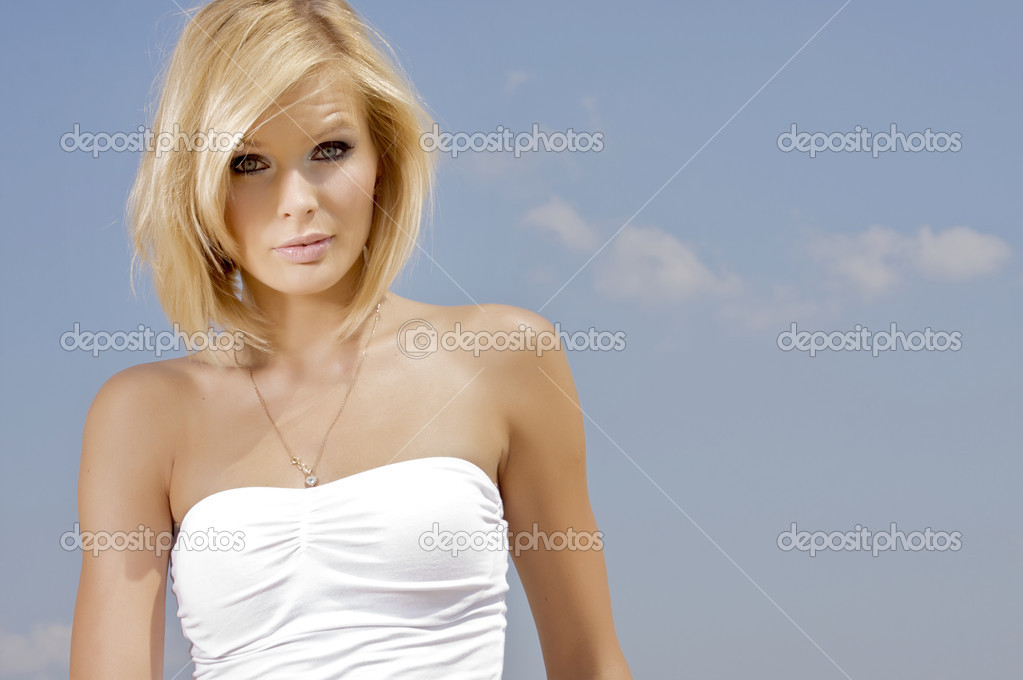 Portrait of beautiful blonde girl on background blue sky — Stock Photo #12043999