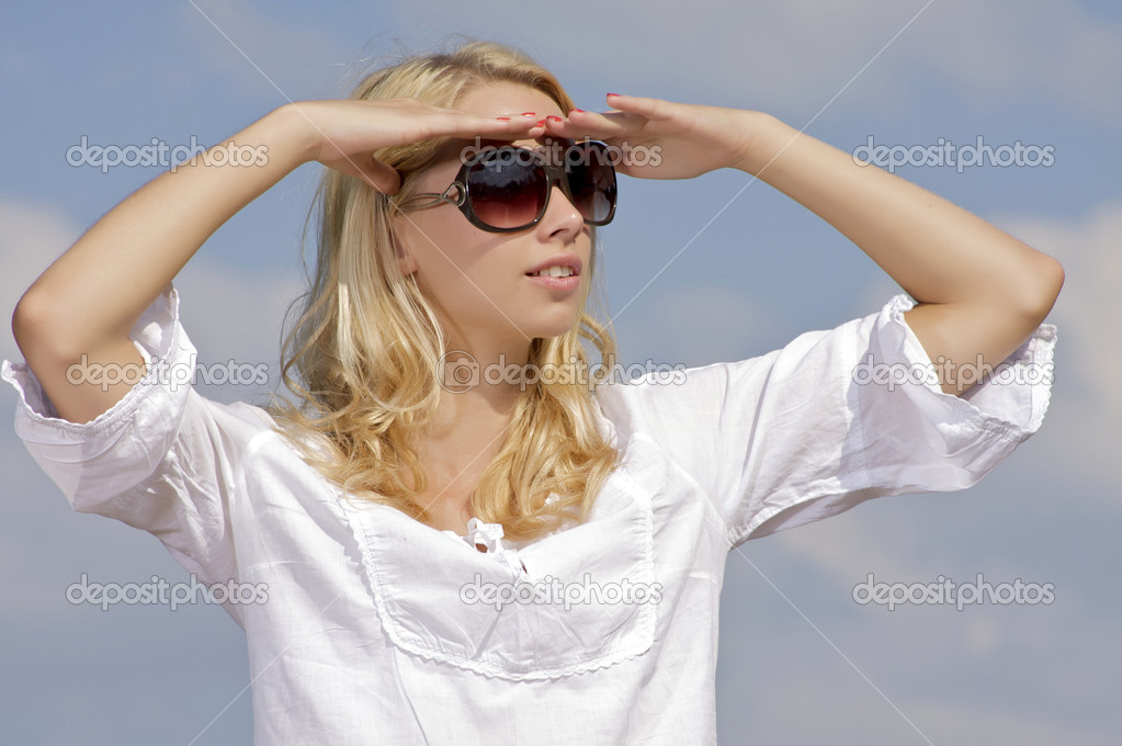 Portrait of beautiful blonde girl in sunglasses on background blue sky  Stock Photo #12044002
