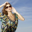 Beautiful girl in sunglasses on background blue sky - Stockfoto
