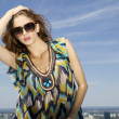 Beautiful girl in sunglasses on background blue sky - Stok fotoğraf