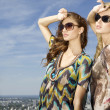 Two beautiful girl in sunglasses on background blue sky - Stok fotoğraf