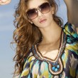Beautiful girl in sunglasses on background blue sky - Stock Photo
