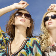 Two beautiful girl in sunglasses on background blue sky — Stock Photo #12067083