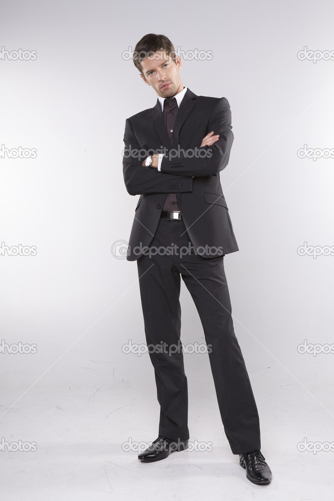 Fashion shot of an elegant young man wearing suit on grey background — Stock Photo #12066581