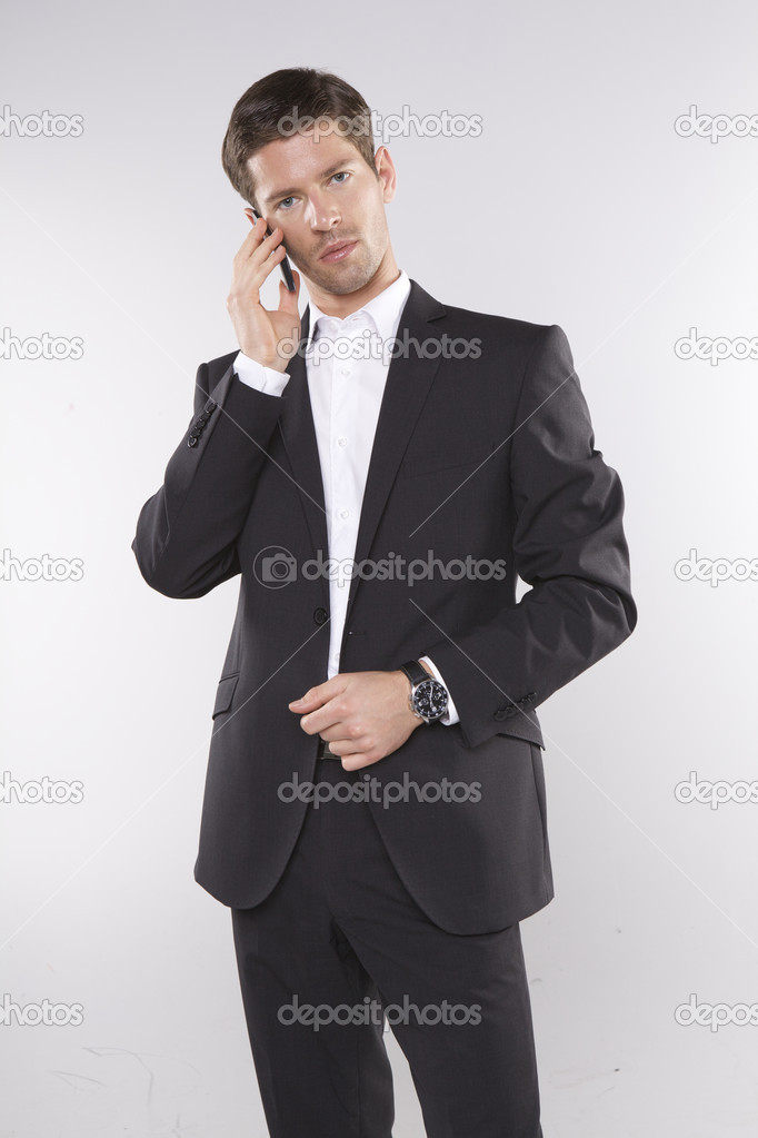 Fashion shot of an elegant young man wearing suit on grey background — Stock Photo #12066728