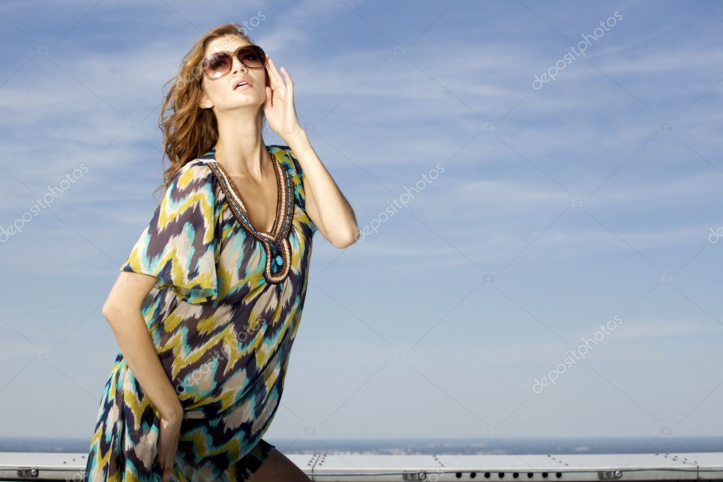 Portrait of beautiful brunette girl in sunglasses on background blue sky — Stock Photo #12066779