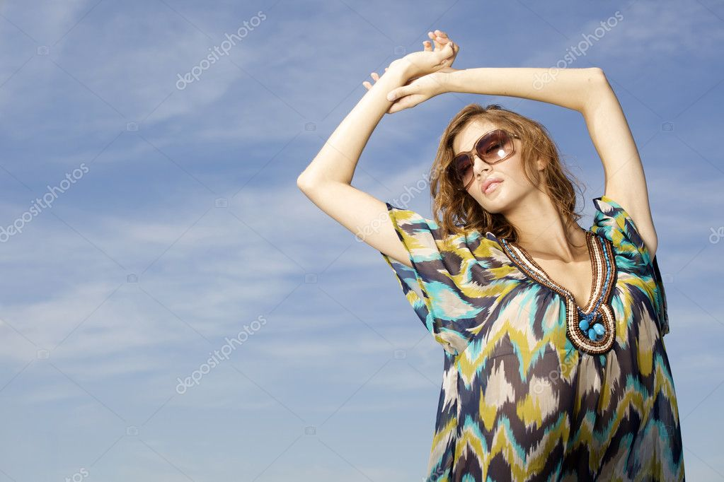 Portrait of beautiful brunette girl in sunglasses on background blue sky — Stock Photo #12066947
