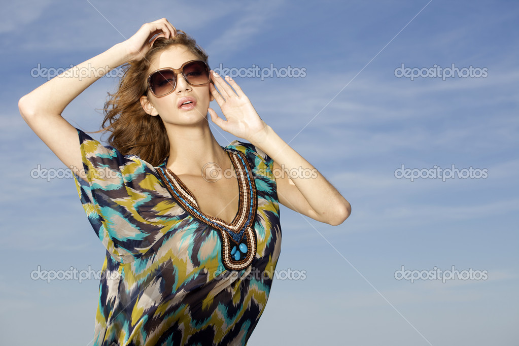 Portrait of beautiful brunette girl in sunglasses on background blue sky — Stock Photo #12066974