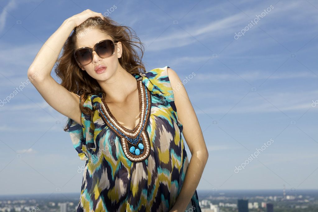 Portrait of beautiful brunette girl in sunglasses on background blue sky  Stock Photo #12066990