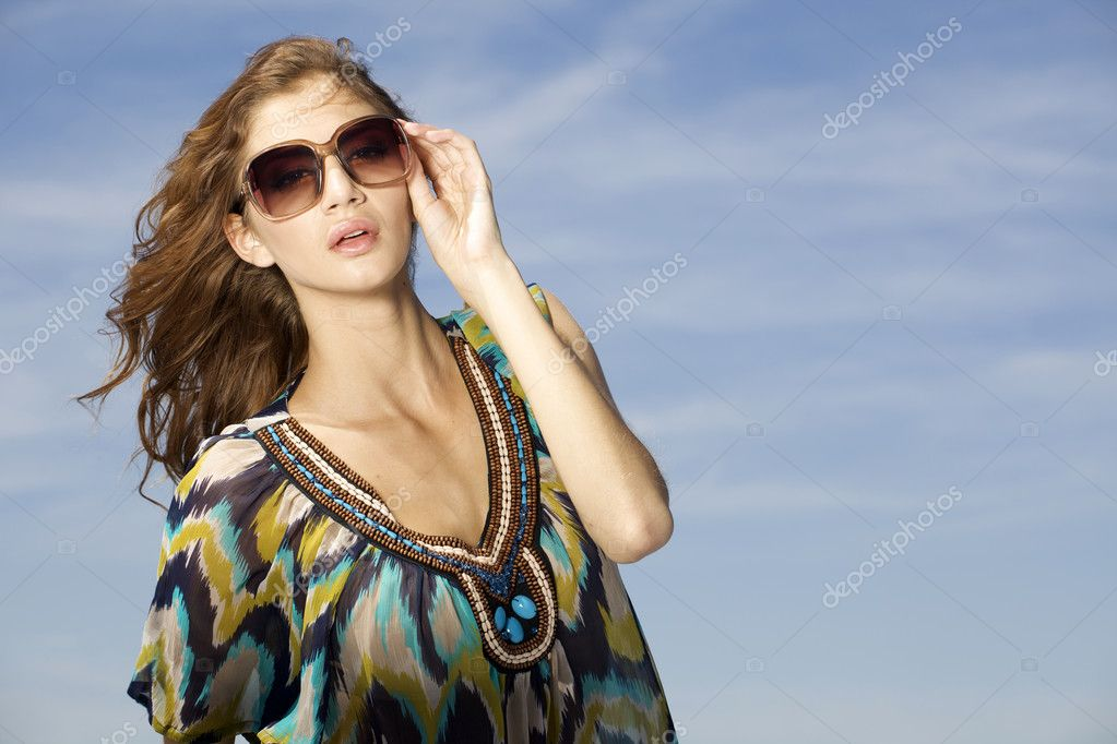 Portrait of beautiful brunette girl in sunglasses on background blue sky — Stock Photo #12066992