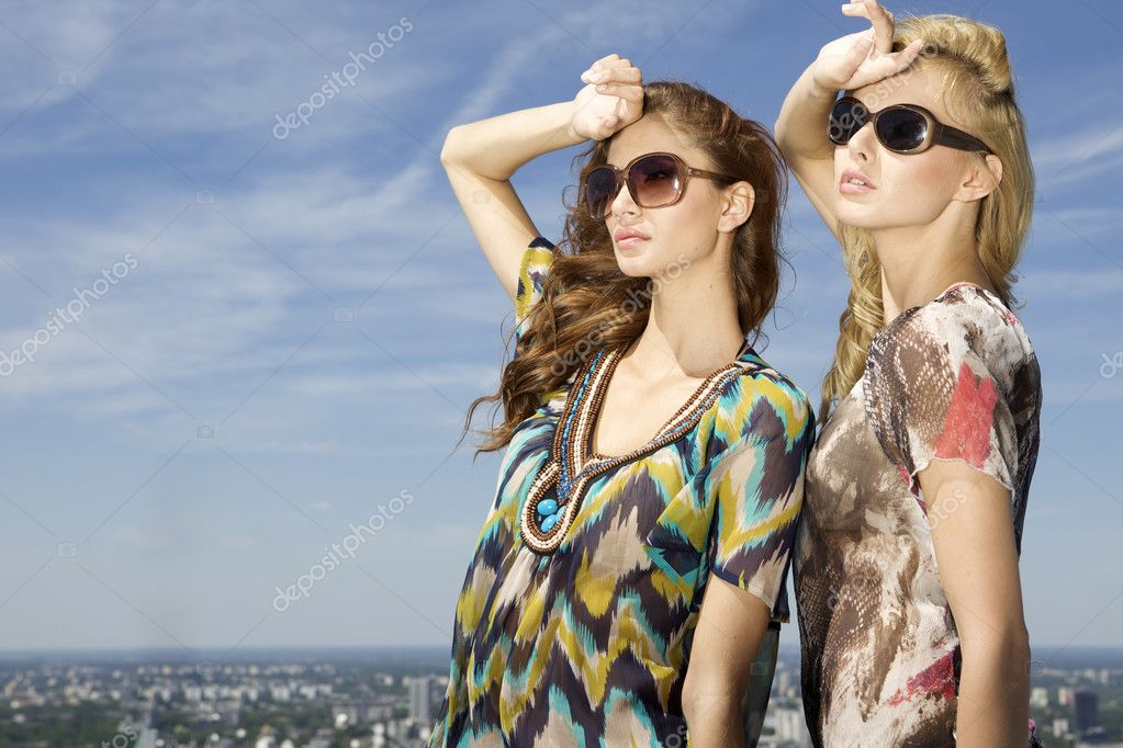 Two beautiful brunette and blonde girl in sunglasses on background blue sky — Stock Photo #12067018
