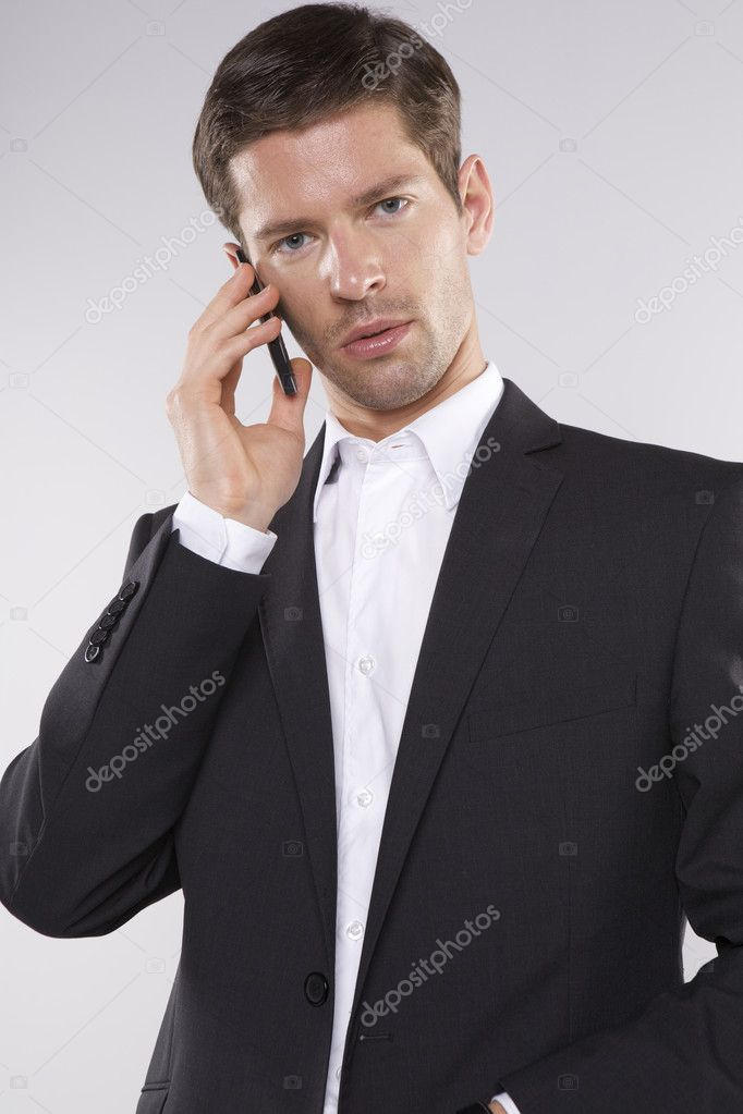 Fashion shot of an elegant young man wearing suit on grey background — Stock Photo #12067022