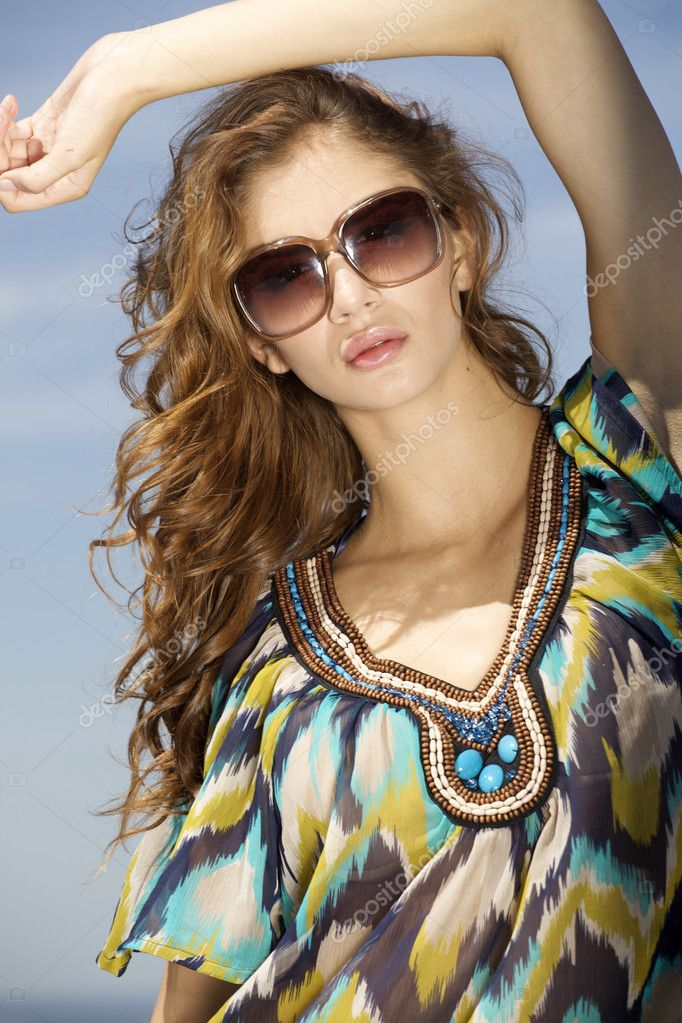 Portrait of beautiful brunette girl in sunglasses on background blue sky — Stock Photo #12067040