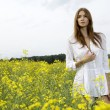 Brunette woman in a yellow flowers field — Stock Photo #12311379