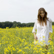 Brunette woman in a yellow flowers field — Stock Photo #12311385