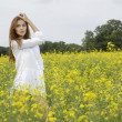 Brunette woman in a yellow flowers field — Stock Photo #12311396